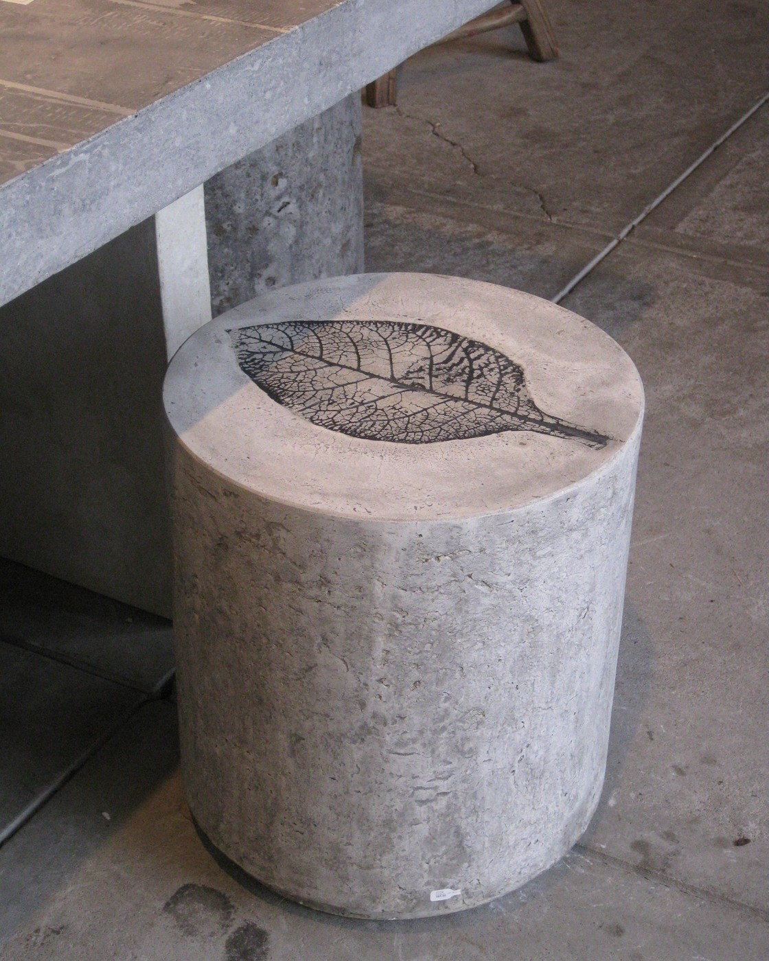 white Concrete stool with black tobacco leaf impression